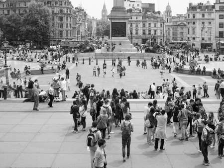 trafalgar: LONDON, UK - JUNE 12, 2015: Tourists visiting Trafalgar Square in black and white Editorial