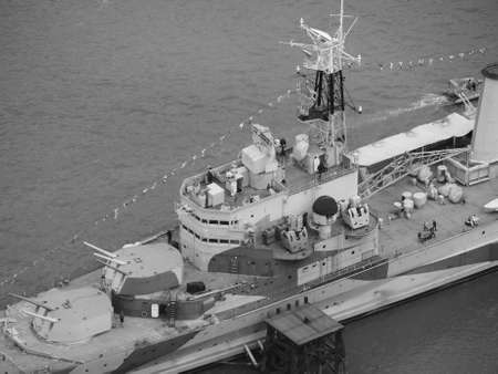 hms: LONDON, UK - JUNE 10, 2015: HMS Belfast ship originally a Royal Navy light cruiser is now permanently moored on the River Thames as a museum ship in black and white