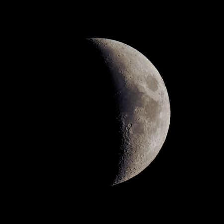 astrophoto: First quarter moon over dark black sky seen with a telescope from northern emisphere at night