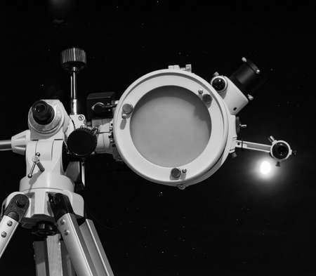 astrophoto: Astronomical telescope over dark sky with the moon - selective focus on telescope in black and white Stock Photo