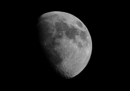 gibbous: Gibbous moon over dark black sky seen with a telescope from northern emisphere at night in black and white Stock Photo