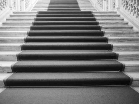occasions: Red carpet on a stairway used to mark the route taken by heads of state, vips and celebrities on ceremonial and formal occasions or events in black and white Stock Photo