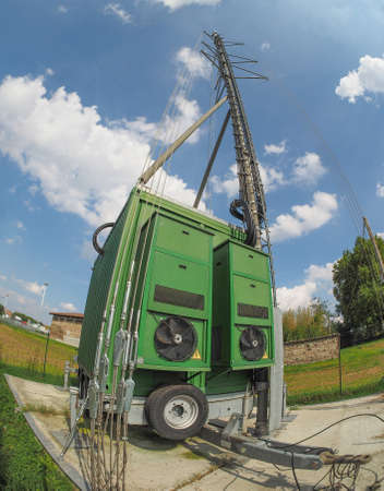 transceiver: Cell on wheels aka COW mobile cell site with cellular antenna tower and electronic radio transceiver equipment part of a cellular network in a rural area seen with fisheye lens