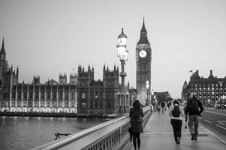 westminster bridge: LONDON, UK - JUNE 10, 2015: People crossing Westminster Bridge over River Thames with Houses of Parliament and Big Ben in the background at night in black and white