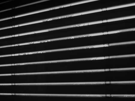 seen: Silhouette of windows blinds seen from a dark room against the sun light Stock Photo