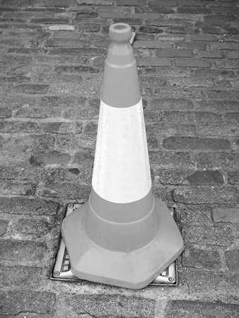 roadworks: Orange and white traffic cone for roadworks in black and white Stock Photo