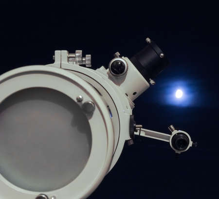 astrophoto: Astronomical telescope over dark sky with the moon - selective focus on telescope