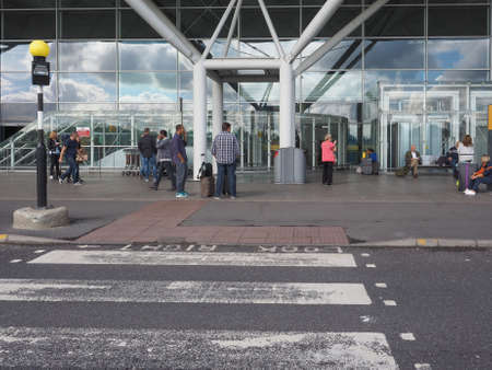 foster: STANSTED, UK - SEPTEMBER 24, 2015: Travellers in front of London Stansted airport design by architect Lord Norman Foster Editorial