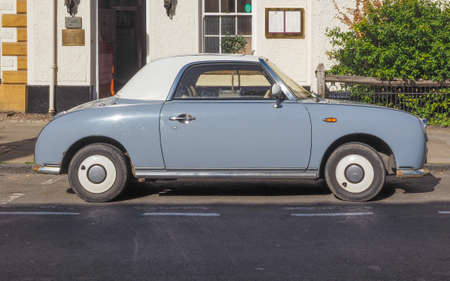 resembling: STRATFORD UPON AVON, UK - SEPTEMBER 26, 2015: Figaro is a small retro car manufactured by Nissan resembling the aesthetics of the sixties cars