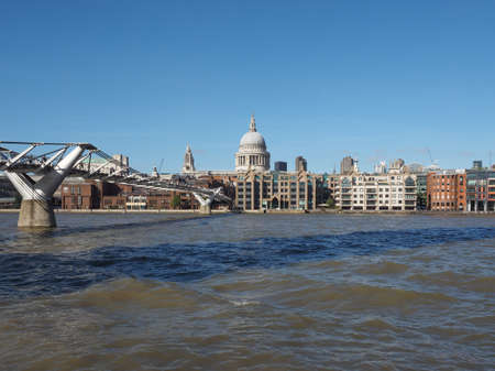 millennium bridge: LONDON, UK - SEPTEMBER 28, 2015: People crossing the Millennium Bridge over River Thames linking the City of London with the South Bank between St Paul Cathedral and Tate Modern art gallery