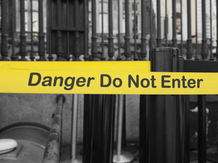 or not: Yellow band fence danger do not enter warning sign Stock Photo