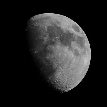 seen: Gibbous moon over dark black sky seen with a telescope from northern emisphere at night in black and white Stock Photo