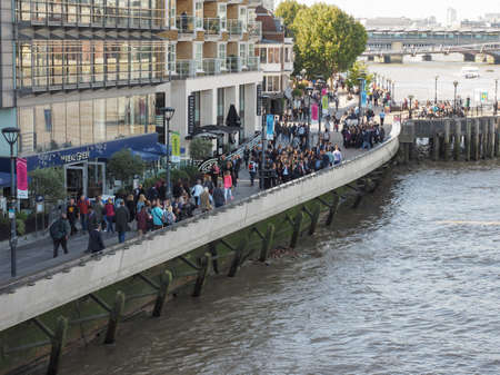 southbank: LONDON, UK - SEPTEMBER 29, 2015: Tourists walking on the River Thames South Bank