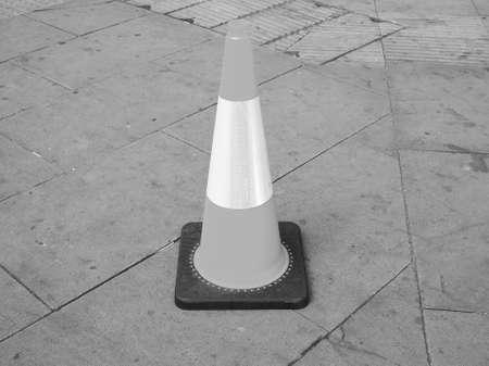 black and white cone: Orange and white traffic cone for roadworks in black and white Stock Photo
