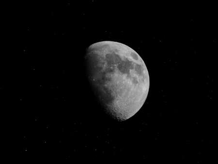 astrophoto: Gibbous moon over dark black sky with stars seen with a telescope from northern emisphere at night in black and white