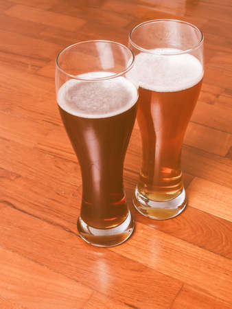 weizen: Vintage looking Two glasses of German dark and white weizen beer on the floor for a romantic rendezvous Stock Photo