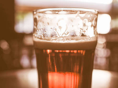 public houses: Vintage looking A pint of beer in a pub, focus on beer and blurred background bokeh Stock Photo