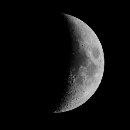 seen: First quarter moon over dark black sky seen with a telescope from northern emisphere at night in black and white Stock Photo