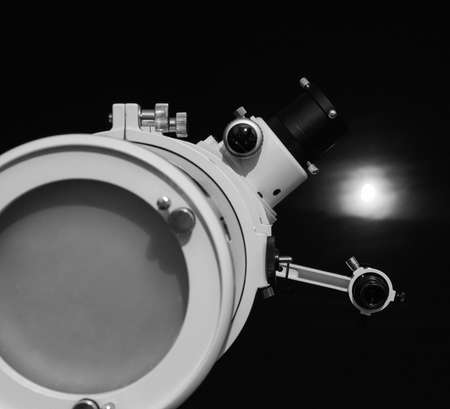 astronomical: Astronomical telescope over dark sky with the moon - selective focus on telescope in black and white Stock Photo