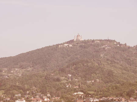 looking at view: Vintage looking View of the hills surrounding the city of Turin, Italy with the Basilica di Superga baroque church on top of the hill Archivio Fotografico