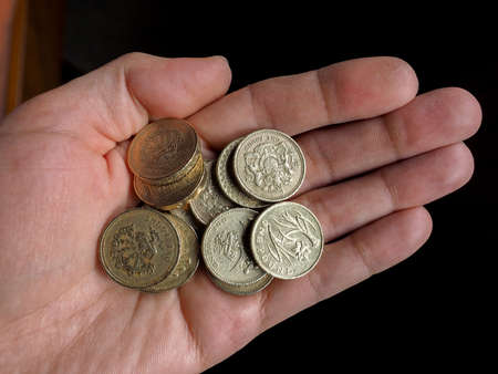 money pound: Hand with British Pound coins currency of the United Kingdom