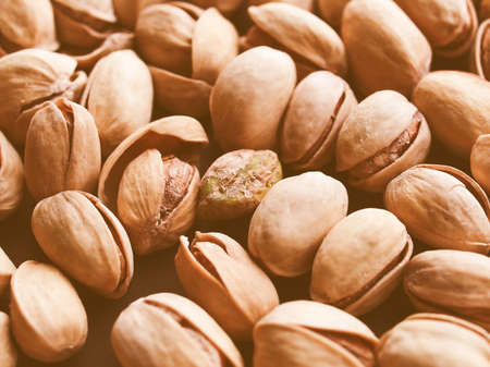 nut shell: Vintage looking Food - Salted roasted pistachio nut with shell - useful as a background Stock Photo