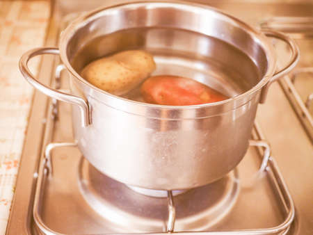 gas cooker: Saucepot with potatoes on a gas cooker vintage