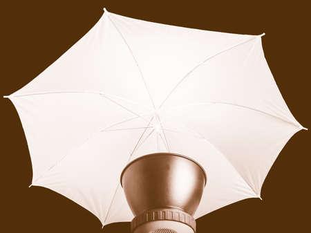 lighting background: Lighting photo umbrella used with strobo lights in photographic studio - over black background vintage