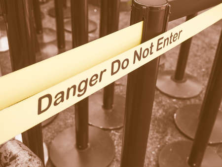 or not: Yellow band fence danger do not enter warning sign vintage