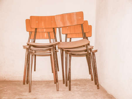stored: Pile of old chairs stored in a cellar against a wall vintage Stock Photo