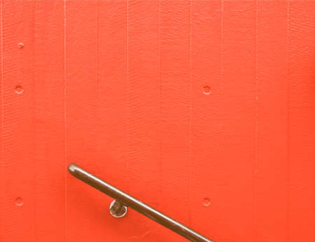hand rails: Handrail over a red painted concrete wall vintage