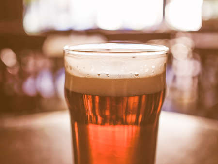 bier: A pint of beer in a pub, focus on beer and blurred background bokeh vintage