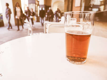 alfresco: A pint of British ale beer on a table at alfresco bar vintage