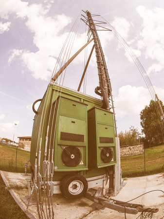 transceiver: Cell on wheels aka COW mobile cell site with cellular antenna tower and electronic radio transceiver equipment part of a cellular network in a rural area seen with fisheye lens vintage