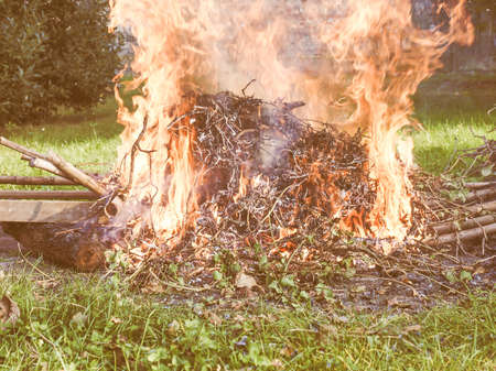 combustible: Bonfire in a meadow amidst the grass vintage Stock Photo