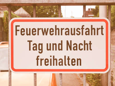 way out: A fire lane road sign in German, meaning to leave exit free all day and night vintage