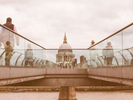 millennium bridge: LONDON, UK - JUNE 10, 2015: People crossing the Millennium Bridge linking the City of London with the South Bank between St Paul Cathedral and Tate Modern art gallery vintage
