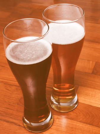 rendezvous: Two glasses of German dark and white weizen beer on the floor for a romantic rendezvous vintage Stock Photo