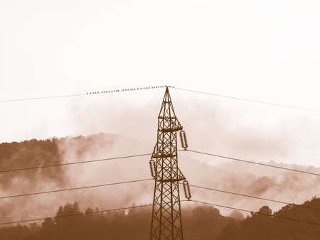 awe: Vintage looking Sublime awe inspiring nature with transmission line in stormy weather in black and white