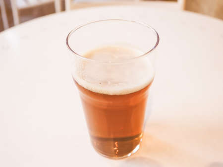 bier: Vintage looking Pint of British ale on a pub table - selective focus on beer over blurred background