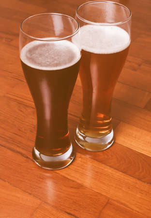 weizen: Two glasses of German dark and white weizen beer on the floor for a romantic rendezvous vintage Stock Photo