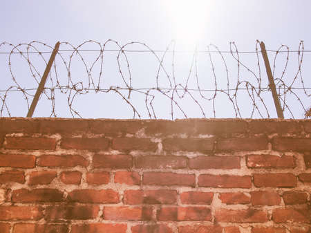 trespass: Sun shining behind a barbed wire fence wall protection, symbol of hope and freedom vintage