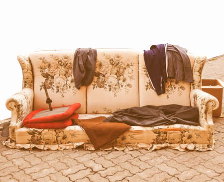 hobo: Old sofa with clothes used by poor homeless hobo vintage