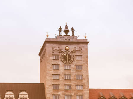 conquers: LEIPZIG, GERMANY - JUNE 14, 2014: Omnia Vincit Labor from Virgil Georgics meaning Work conquers all - written on the Krochhochhaus built in 1927 as the first skyscraper in the city vintage