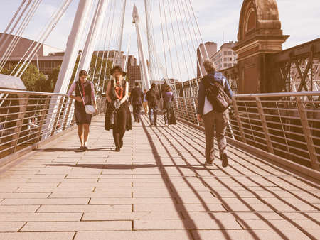 linking: LONDON, UK - SEPTEMBER 29, 2015: People crossing the Jubilee Bridge over River Thames linking Charing Cross to the South Bank and Waterloo vintage