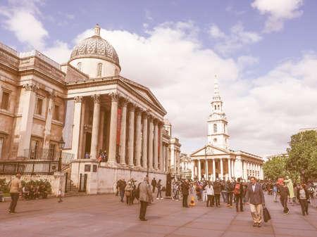 trafalgar: LONDON, UK - JUNE 09, 2015: Tourists visiting Trafalgar Square in front of the National Gallery vintage