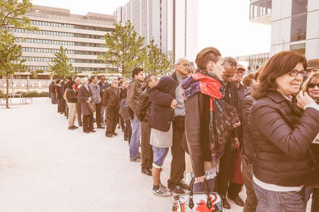 queueing: TURIN, ITALY - APRIL 11, 2015: People queueing to visit the new Intesa San Paolo skyscraper designed by Renzo Piano Building Workshop which just opened today and is the highest building in Turin vintage Editorial