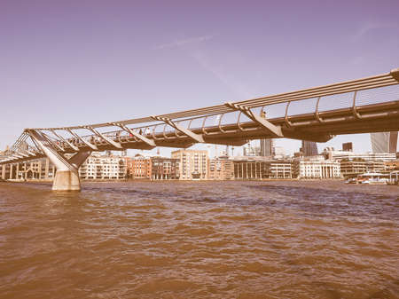 millennium bridge: LONDON, UK - SEPTEMBER 28, 2015: People crossing the Millennium Bridge over River Thames linking the City of London with the South Bank between St Paul Cathedral and Tate Modern art gallery vintage Editorial