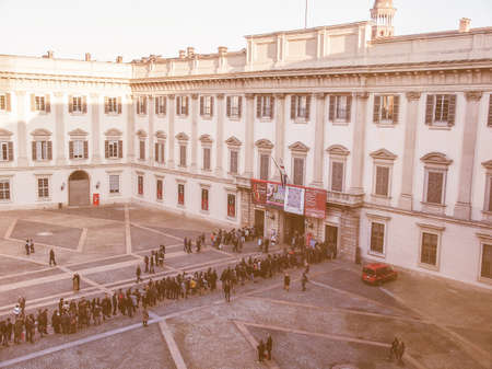 queueing: MILAN, ITALY - FEBRUARY 23, 2014: People queueing in front of Palazzo Reale exhibition room to visit a temporary exhibition vintage Editorial