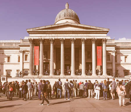 trafalgar: LONDON, UK - SEPTEMBER 27, 2015: Tourists in Trafalgar Square in front of the National Gallery vintage